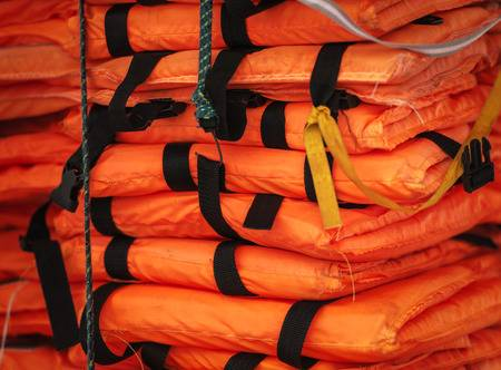27593470-close-up-view-of-packed-orange-life-jackets-pile-ready-for-shipping-string-with-hook-holding-jacket-